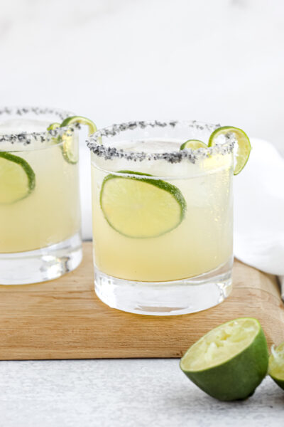 Two Easy Skinny Margaritas with salted rims sitting on a wooden tray