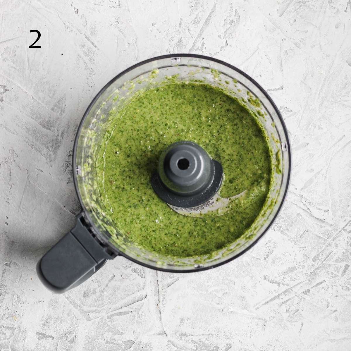 a food processor with blended dairy free pesto inside