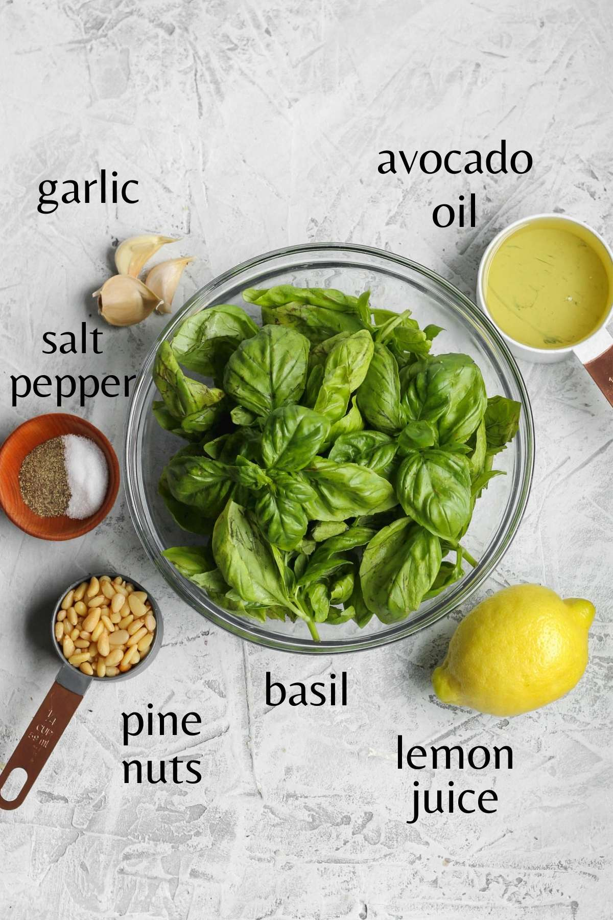 Fresh basil in a glass bowl with avocado oil in a measuring cup, garlic cloves, a lemon, pine nuts in a measuring cup, and salt and pepper in a small bowl sitting next to it