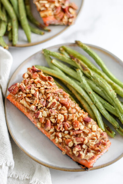 A grey plate with Pecan Crusted Honey Mustard Salmon and green beans