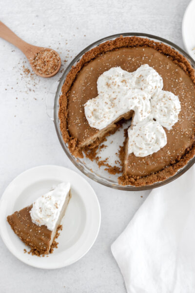 Easy Gluten and Dairy Free Coconut Cream Pie piece sitting on a small plate pointing toward the whole pie