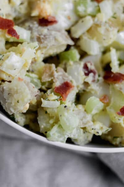 A bowl of Whole30 Loaded Potato Salad filled with potatoes, celery, bacon, onion, and hard boiled eggs.