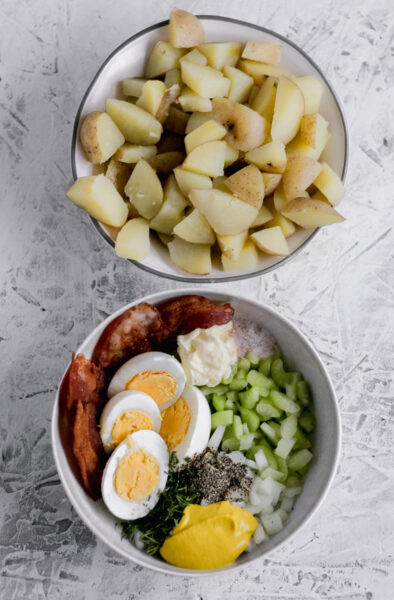 Two bowl filled with Whole30 Loaded Potato Salad ingredients. One with diced potatoes, the other with hard boiled eggs, bacon, diced celery and onions, mustard, mayo, vinegar, salt, pepper, and dill