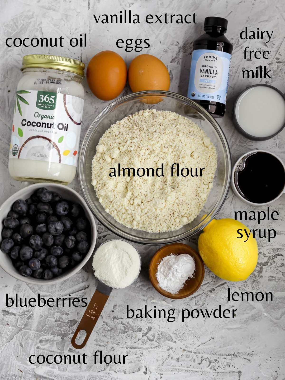 A bowl with almond flour, a small bowl with blueberries, a jar of coconut oil. 2 eggs, a bottle of vanilla extract, a small cut of dairy free milk, a small cup of maple, syrup, a lemon, a small cup with coconut flour, and a small bowl with baking powder