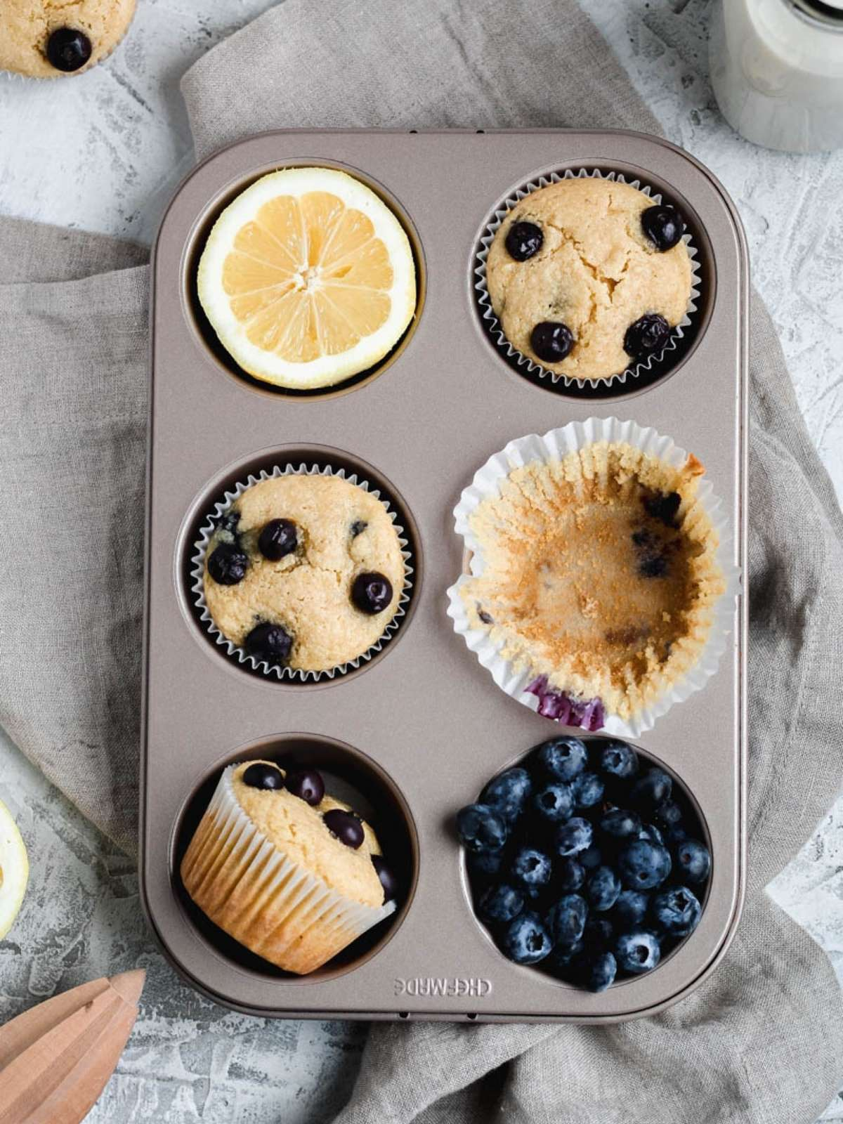 A six muffin tin pan filled with three gluten free blueberry lemon muffins, one tin is filled with a sliced lemon, one tin is filled with an empty cupcake liner, and one tin is filled with blueberries