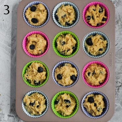 A muffin pan with each tin filled with muffin mixture