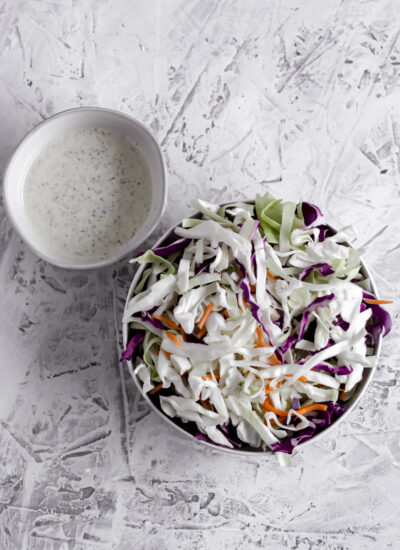 A bowl of shredded cabbage and a small bowl off to the top left with coleslaw dressing