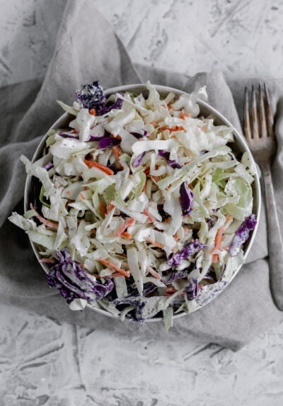 A big bowl of Whole30 Creamy Coleslaw sitting on a towel with a fork off to the right of the bowl