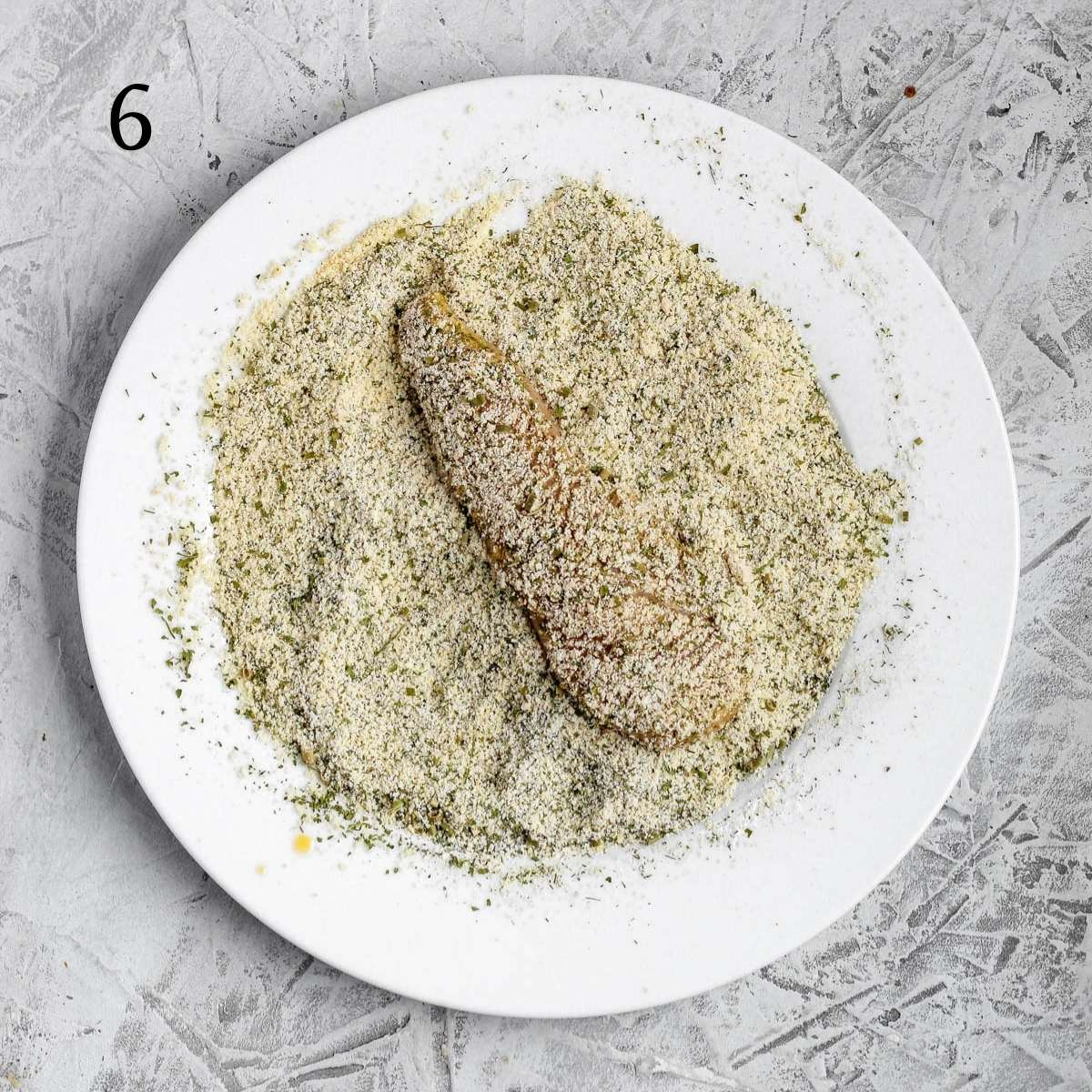 a almond flour mixture on a plate with a chicken tender on top mixed with the almond flour mixtre