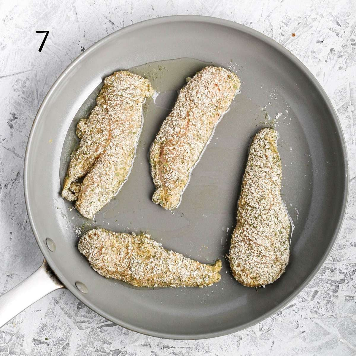 a skillet pan with chicken tenders coated in a almond flour mixture