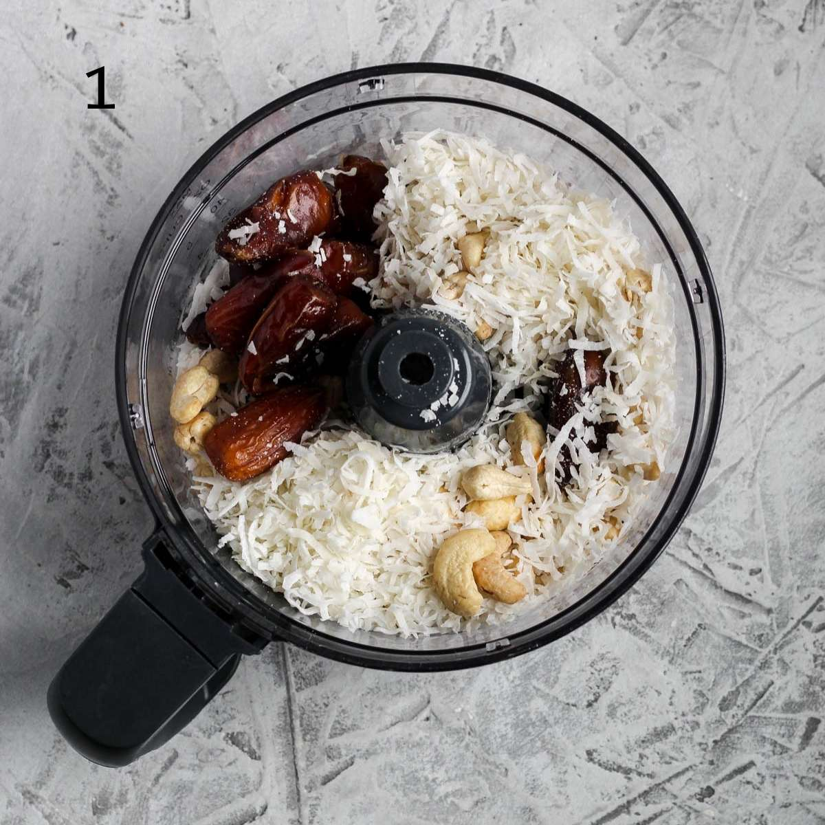 a food processor filled with pitted dates, shredded coconut, cashews, almonds, and coconut oil