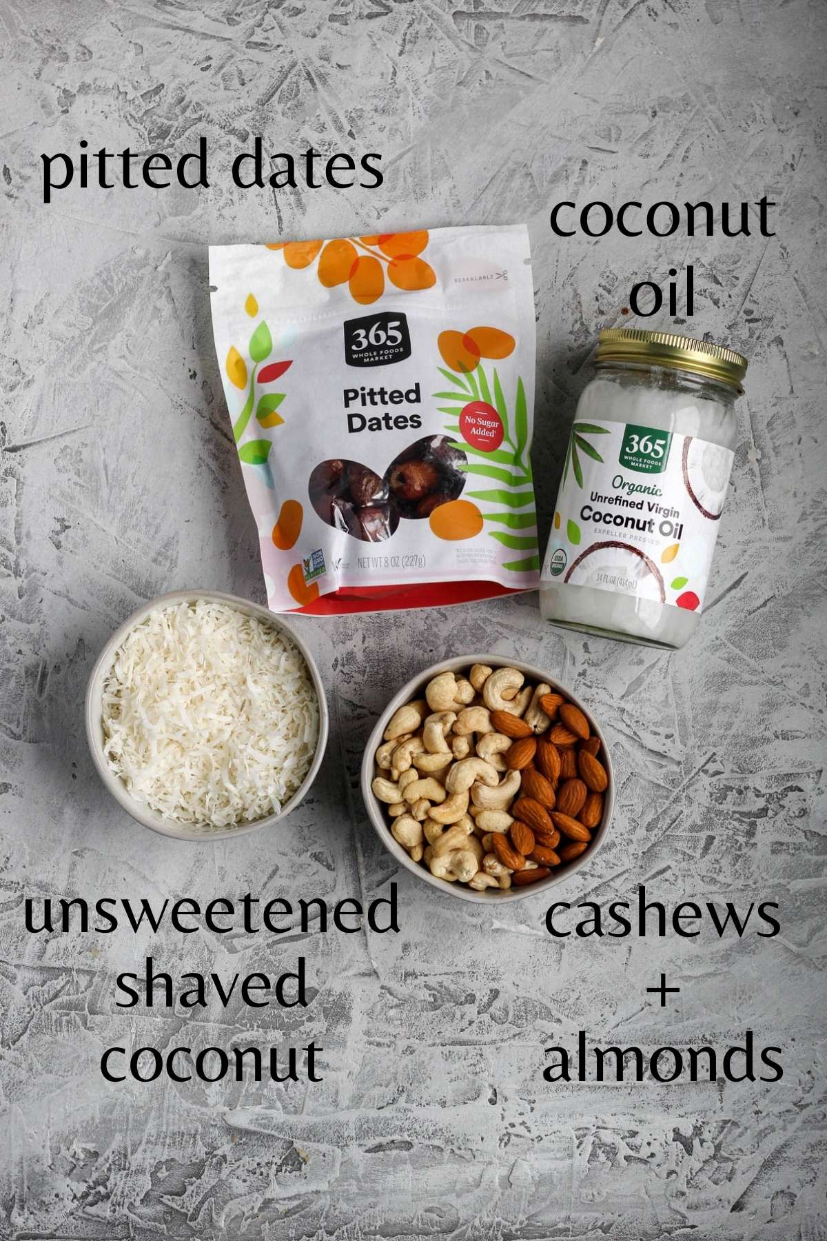 a bag of pitted dates, a jar of coconut oil, a bowl of unsweetened shaved coconut, and a bowl of cashews and almonds