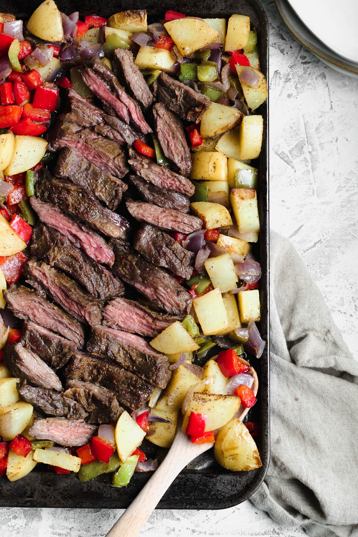 a cooking sheet filled with cooked skirt steak and roasted potatoes and onions