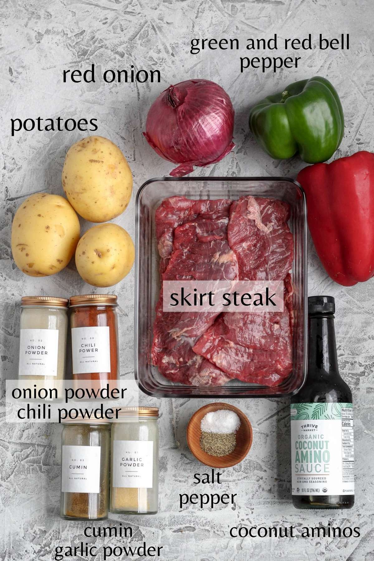 yukong gold potatoes, a red onion, a green bell pepper, coconut aminos. skirt steak, salt, pepper, onion powder, chili powder, cumin, and garlic powder all laying on a flat bakground