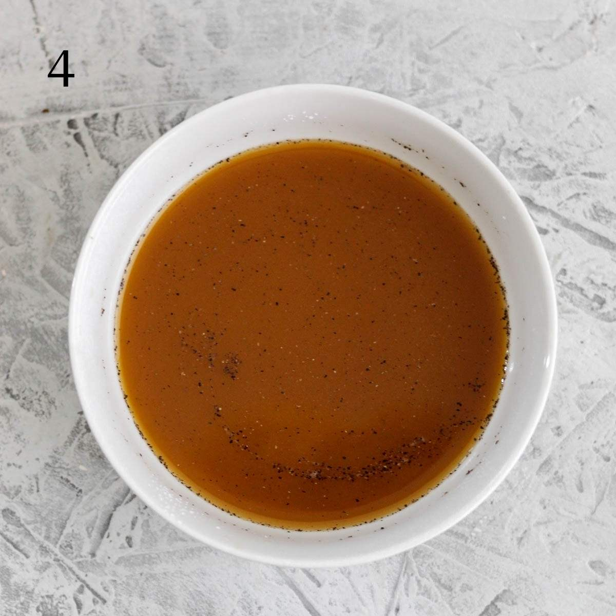 a small bowl with beef broth, coconut aminos, salt, and pepper mixed together